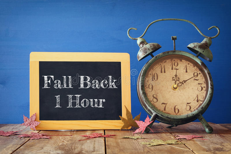 Image of autumn Time Change. Fall back concept. Dry leaves and vintage alarm Clock on rustic wooden table royalty free stock photos