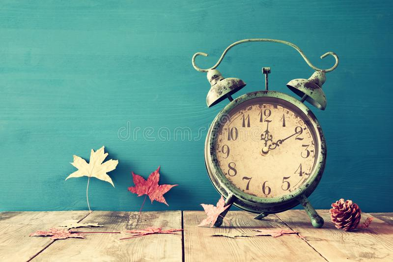 Image of autumn Time Change. Fall back concept. Dry leaves and vintage alarm Clock on rustic wooden table stock image