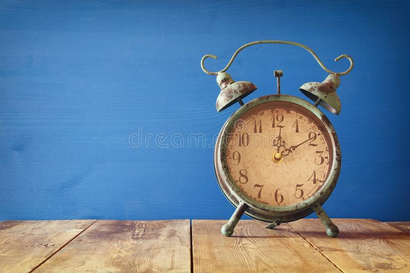 Image of autumn Time Change. Fall back concept. Dry leaves and vintage alarm Clock on rustic wooden table stock photo