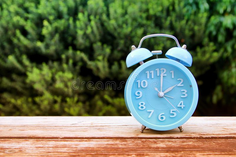 Image of autumn Time Change. Fall back concept. Dry leaves and vintage alarm Clock on wooden table. Outdoors at afternoon royalty free stock photos