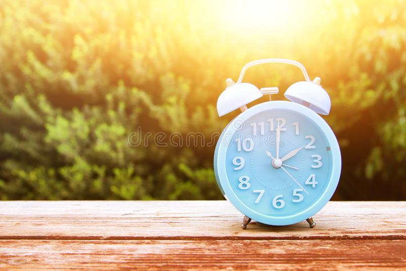 Image of autumn Time Change. Fall back concept. Dry leaves and vintage alarm Clock. On wooden table outdoors at afternoon royalty free stock image