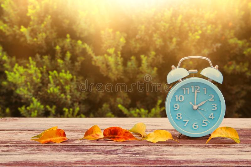 Image of autumn Time Change. Fall back concept. Dry leaves and vintage alarm Clock on wooden table outdoors at afternoon royalty free stock image