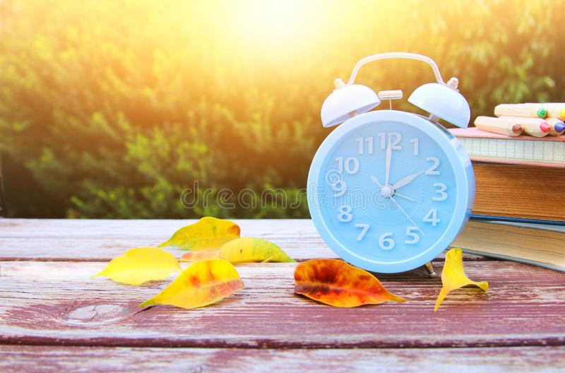 Image of autumn Time Change. Fall back concept. Dry leaves and vintage alarm Clock on wooden table. Outdoors at afternoon stock photography