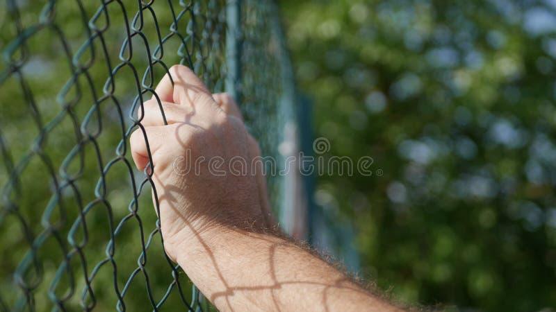 Image avec des mains de l'homme sur une barrière métallique photos libres de droits