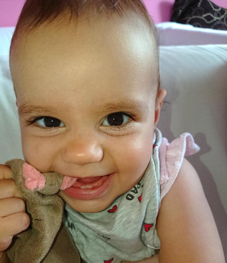 Baby girl teething and chewing on her favorite soft toy. stock photo
