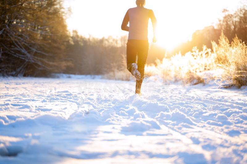 Image from back of man in sportswear, red cap on run in winter royalty free stock photos
