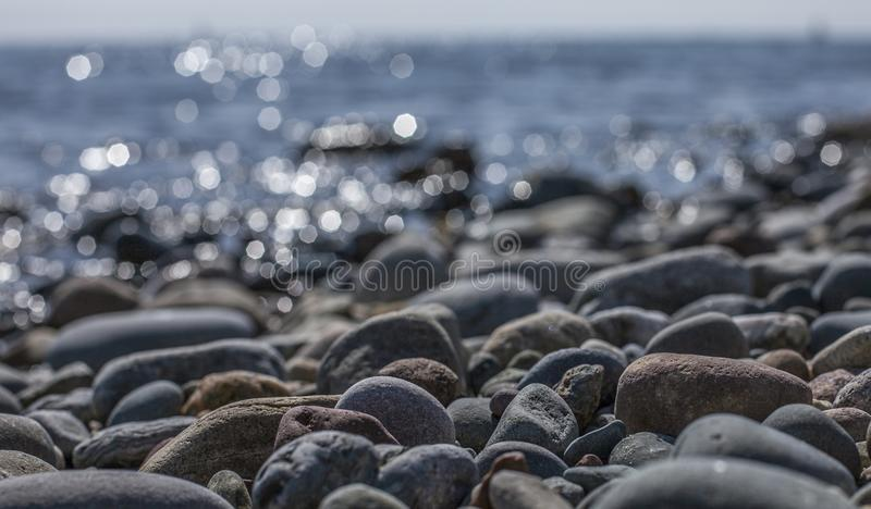 Llanbedrog, Wales, the UK - the stones and shiny waters. This image a beach in LLanbedrog, North Wales. It was taken on a sunny day in spring 2018. We can see stock photos