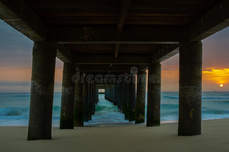 Under the pier. Image of a beach under the pier in the sunrise for backgrounds stock photos