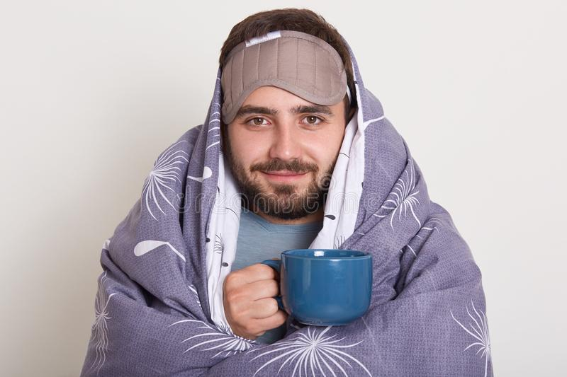 Image of bearded Caucasian young man with blindfold on forehead, unshaven male with moustache, holding blue coffee cup or mug, royalty free stock photos