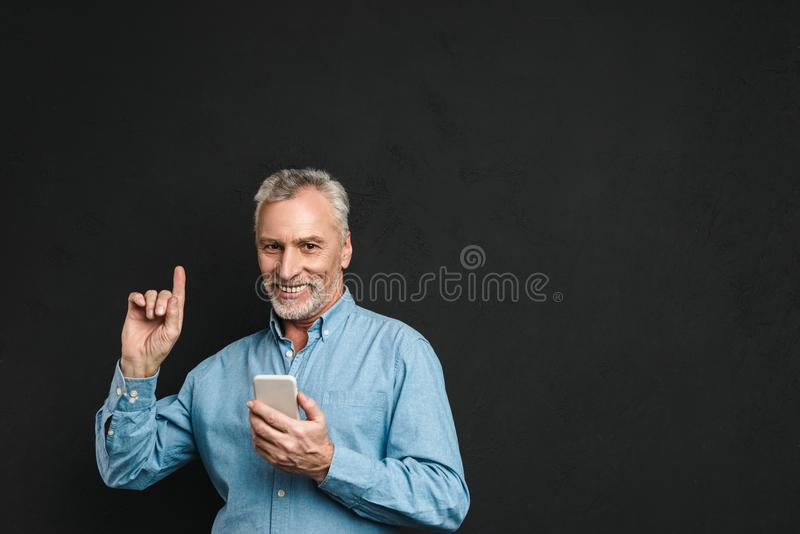 Image of bearded male pensioner 60s with gray hair pointing finger upward like have idea while using mobile phone, isolated over royalty free stock image