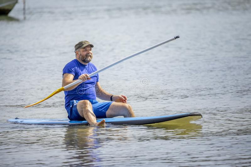 A bearded man paddling in the ocean stock photography