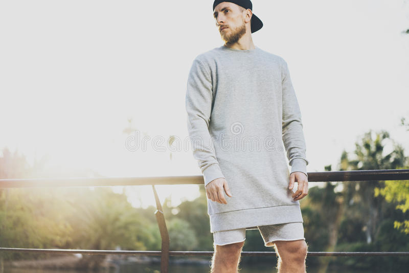 Image Bearded Muscular Man Wearing Gray Empty sweetsh, snapback cap and shorts in summer holiday. Chilling time near the. Lake. Green City Garden Park Sunset stock photography