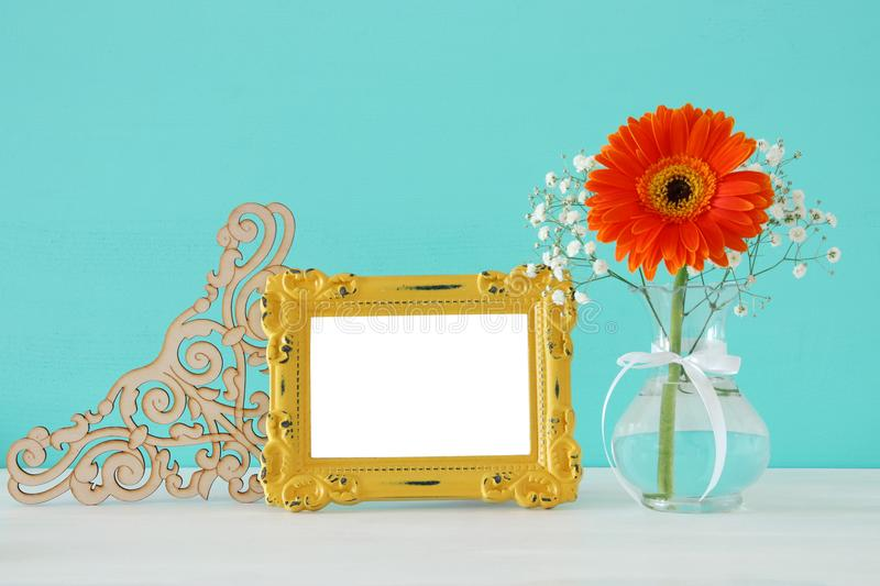 Image of beautiful bouquet of spring flowers next to blank vintage photo frame on wooden table. For photography mock up montage. Image of beautiful bouquet of stock photography