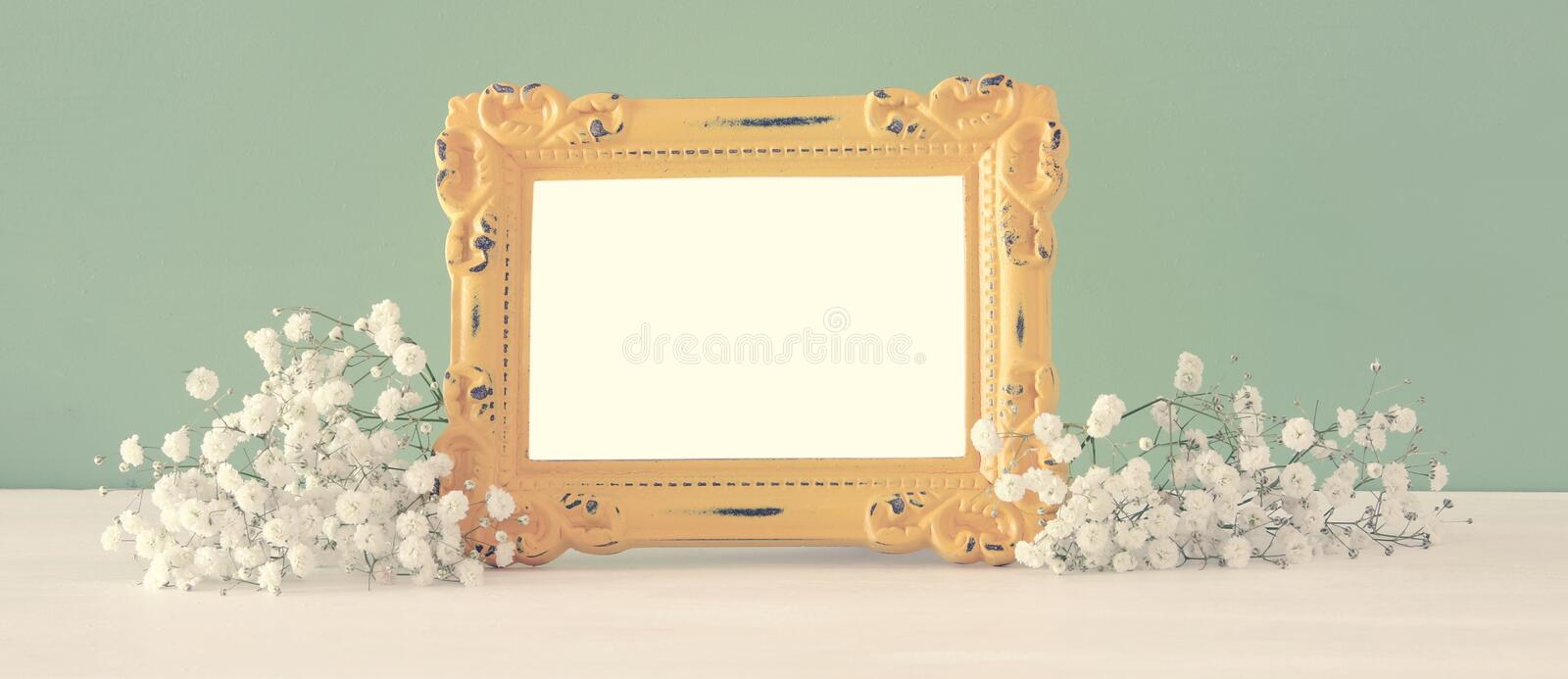 Image of beautiful bouquet of spring flowers next to blank vintage photo frame on wooden table. For photography mock up montage. royalty free stock photo