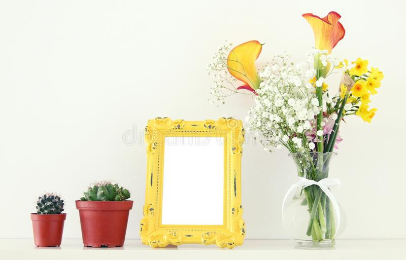 Image of beautiful bouquet of yellow spring flowers next to blank vintage photo frame over white table. For photography mock up mo. Ntage stock images