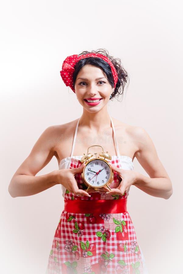 Image of beautiful brunette pinup girl having fun wearing apron holding alarm clock in hands stock photos