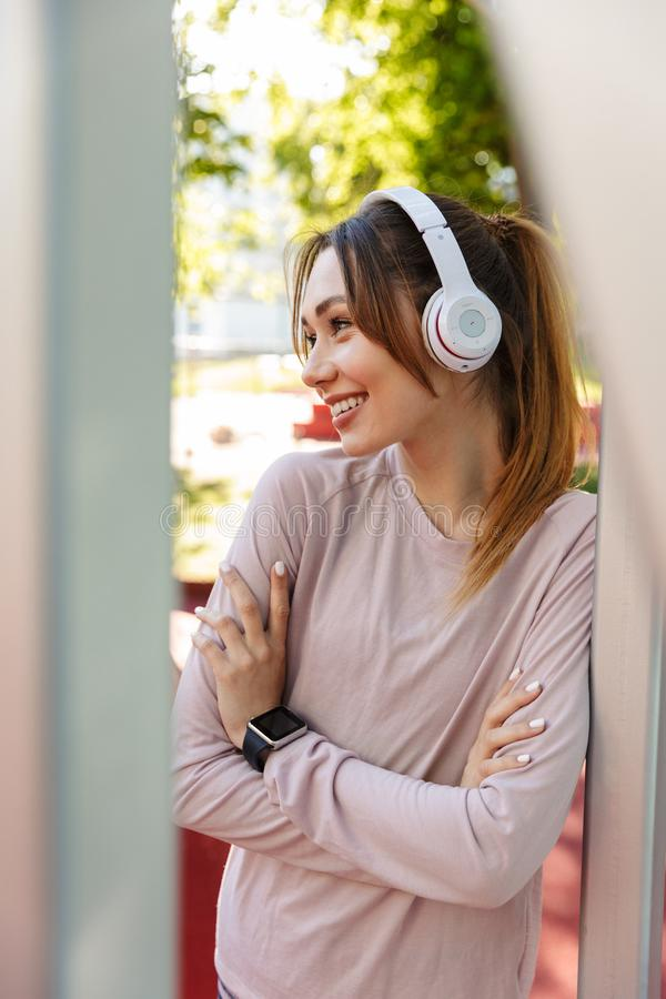 Beautiful cheerful young fitness sports woman posing outdoors in park listening music with earphones royalty free stock photography