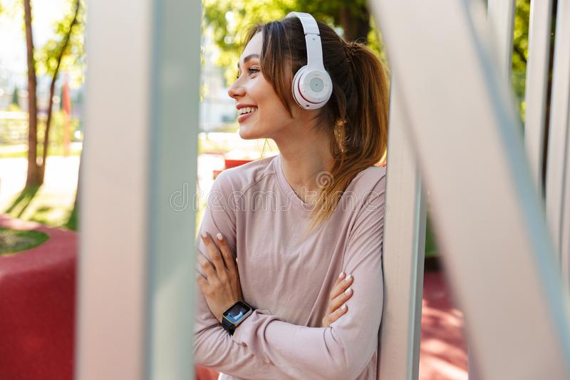 Beautiful cheerful young fitness sports woman posing outdoors in park listening music with earphones royalty free stock image