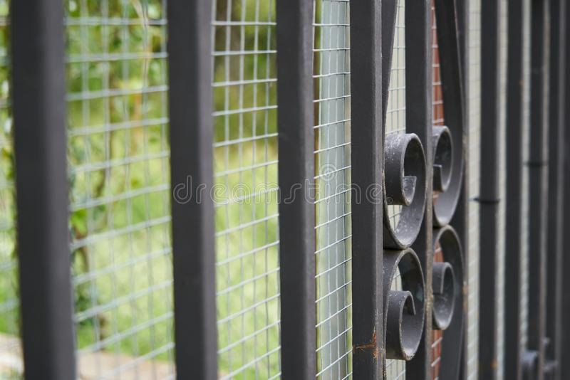 Image of a Beautiful decorative cast iron wrought fence with artistic forging. Metal guardrail close up. Old, architecture, safety, antique, wall, ornate stock photography