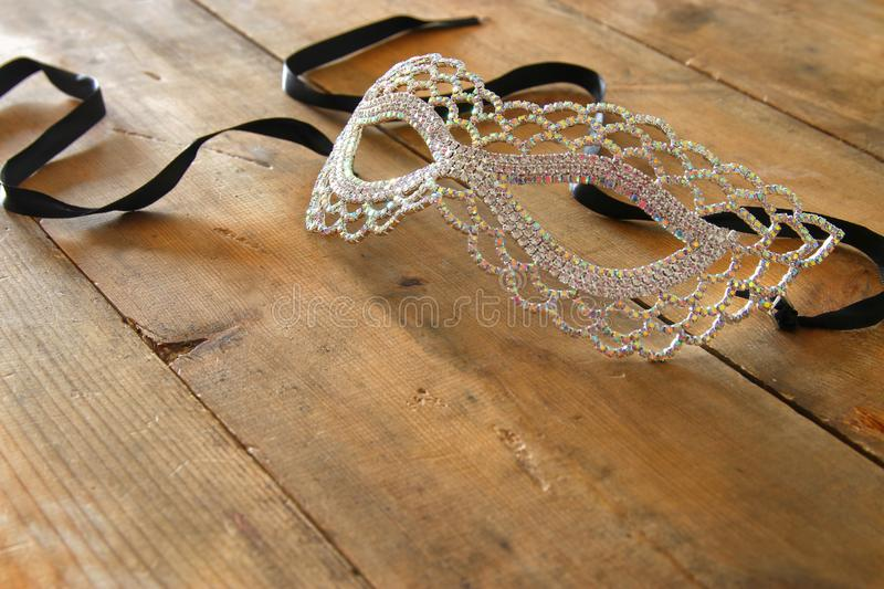 image of beautiful diamond masquerade venetian mask over wooden vintage background. royalty free stock photo