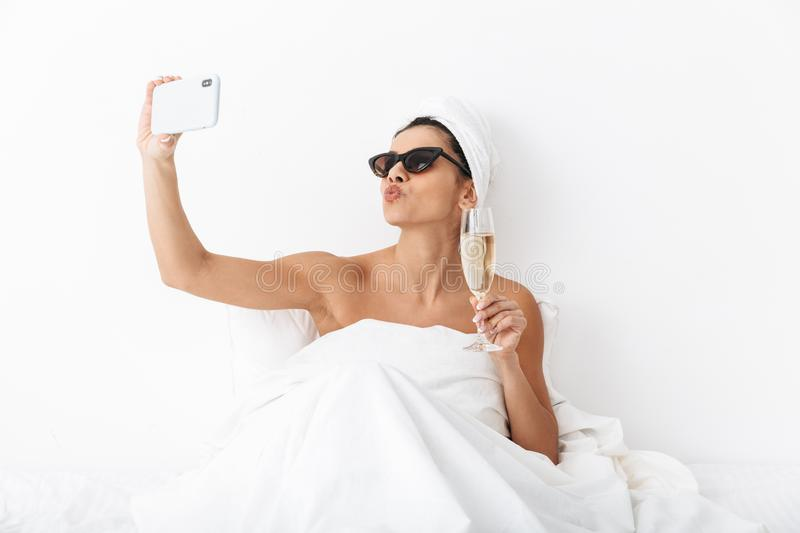 Beautiful emotional woman with towel on head lies in bed under blanket isolated over white wall background wearing sunglasses take royalty free stock photography