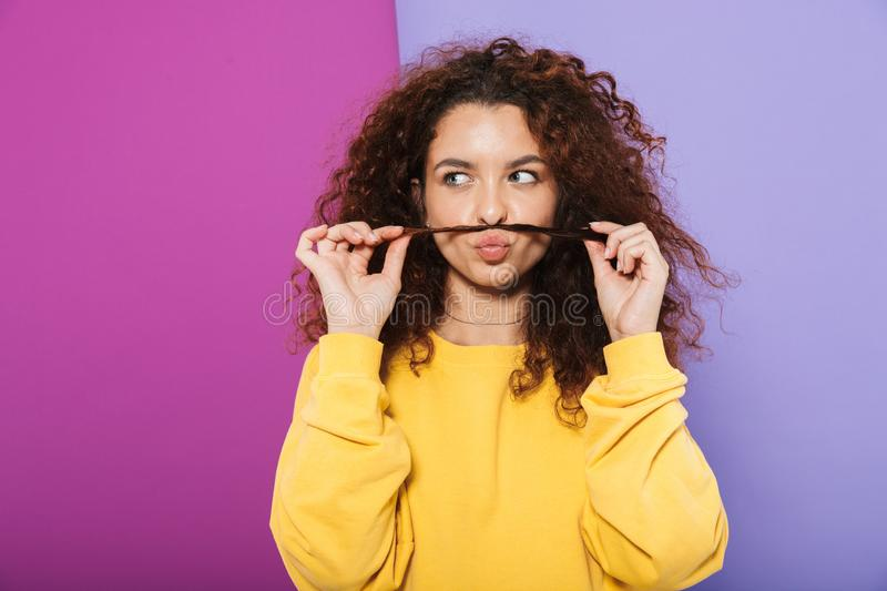 Image of beautiful happy curly woman swearing casual clothes smiling and having fun with her hair royalty free stock photography