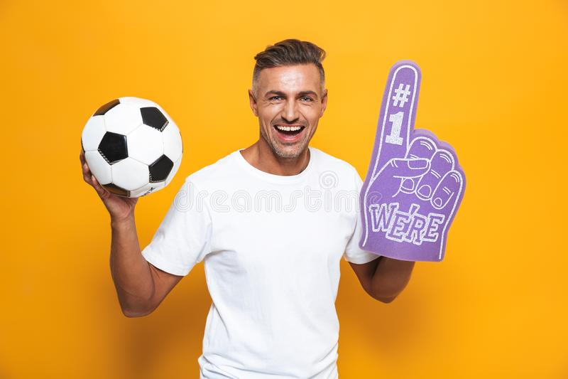 Image of beautiful man 30s in white t-shirt holding soccer ball and number one fan hand glove with finger raised while standing. Isolated over yellow background stock photo