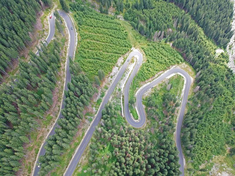The image of a beautiful mountain road. Many conifers along the road. Photo taken in a summer day, from high height. In Romania, Europe- Transalpina royalty free stock photos