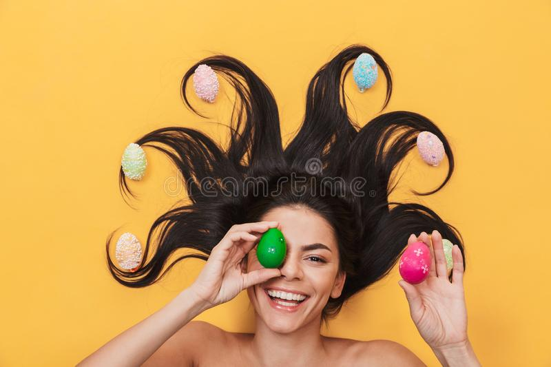 Pleased happy young woman lies isolated on yellow background over easter eggs royalty free stock images