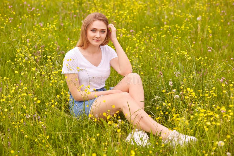 Image of beautiful pretty happy smiling girl sitting on green summer meadow and looking directly at camera, attractive female stock photography