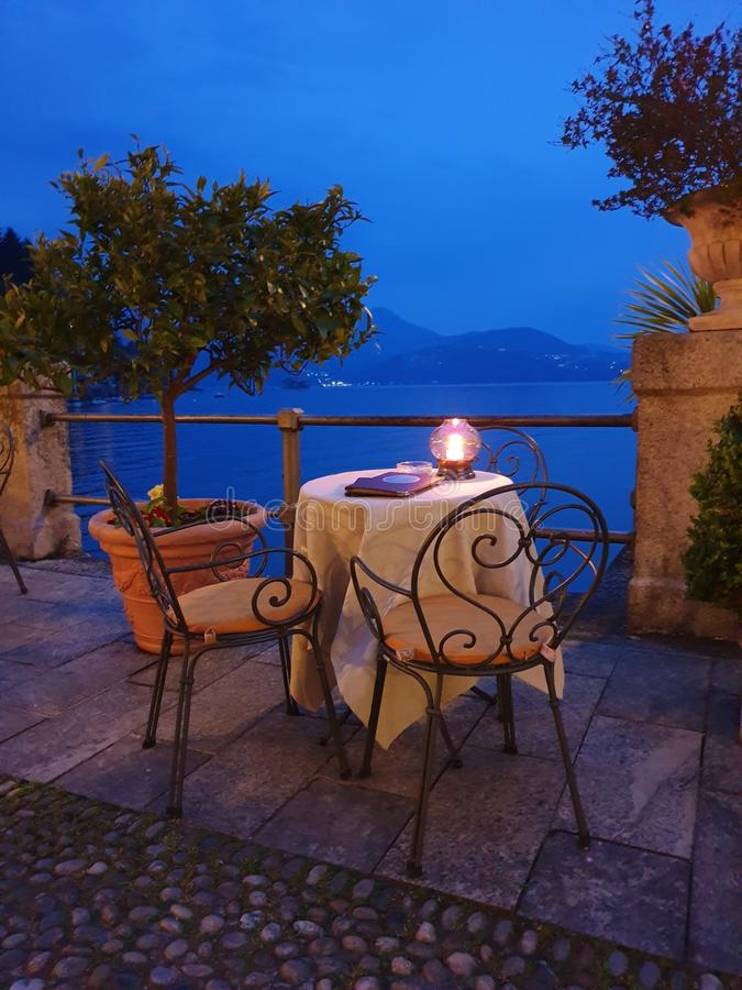 Image of beautiful promenade with candle light dinner arrangement in the evening. At lake maggiore, italy, europe stock photography