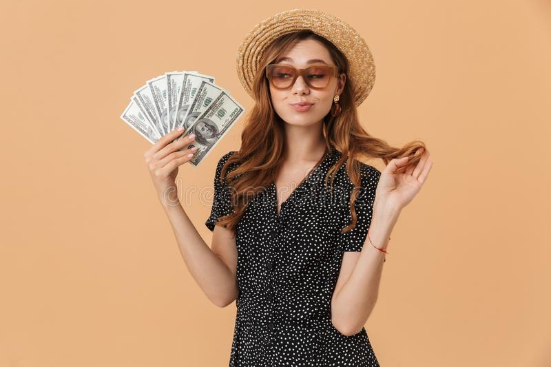 Image of beautiful rich woman 20s wearing straw hat and sunglasses smiling and holding fan of dollar money, isolated over beige b stock image