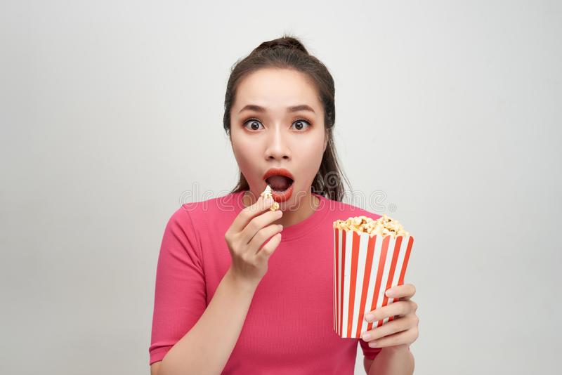 Image of beautiful shocked young pretty woman posing isolated over white background wall holding popcorn eat watch tv film royalty free stock photos