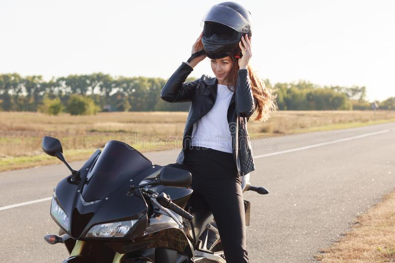 Image of beautiful slender young risk taker sitting on her motorcycle, having trip on her vehicle, fond of extreme activities,. Wearing helmet off, standing at stock photo
