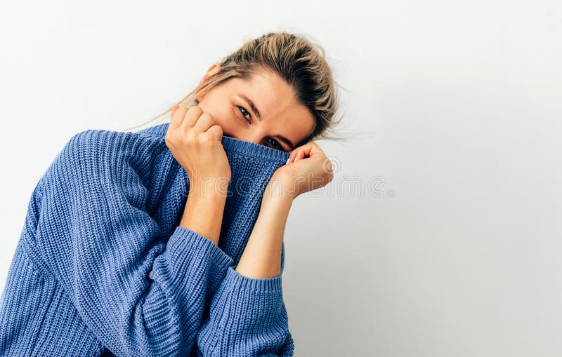 Image of beautiful smiling young woman pulling her blue trendy sweater over head having fun. Joyful female with tied hair in royalty free stock images