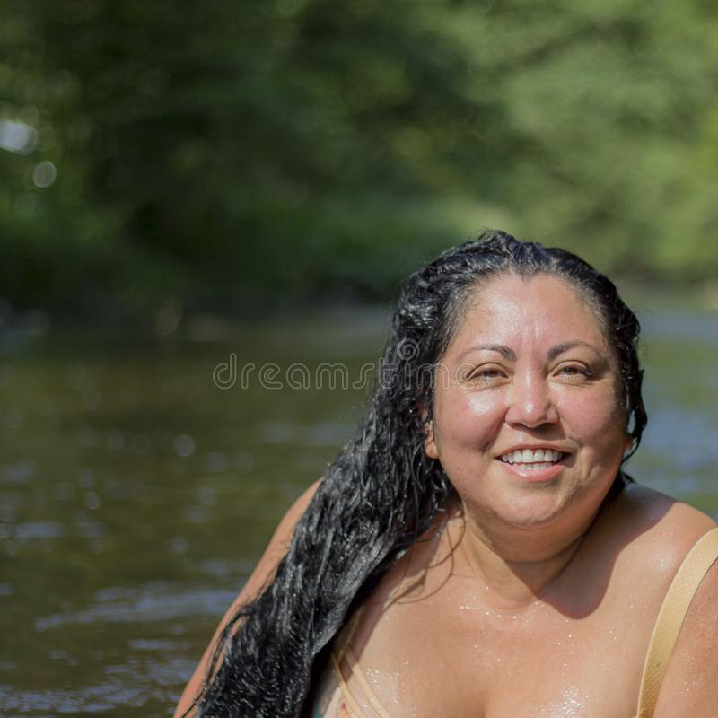 Image of a beautiful tanned woman with long black hair smiling on a wonderful day stock images