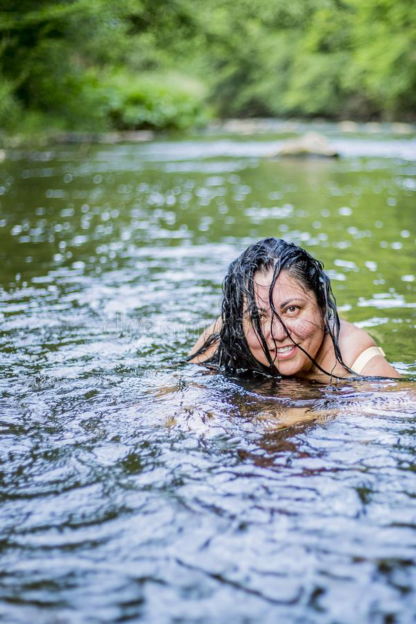 Image of a beautiful woman with long black hair partly in her face enjoying a day in the river stock photography