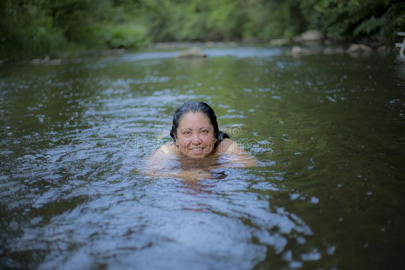 Image of a beautiful woman with long black hair swimming in the river royalty free stock photography