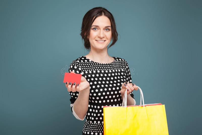 Image of beautiful woman in speckled clothes standing with purchases and cutaway in hands royalty free stock photography