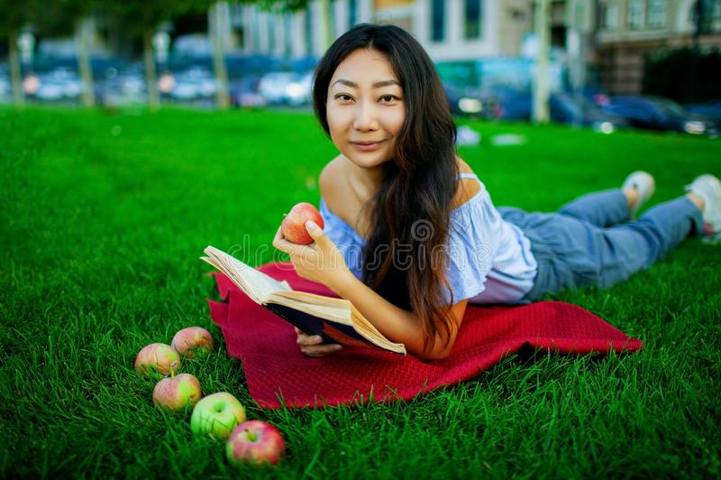 Image of a beautiful young pretty woman lies on grass in park outdoors reading book. stock photo