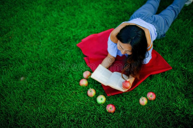 Image of a beautiful young pretty woman lies on grass in park outdoors reading book. stock photos