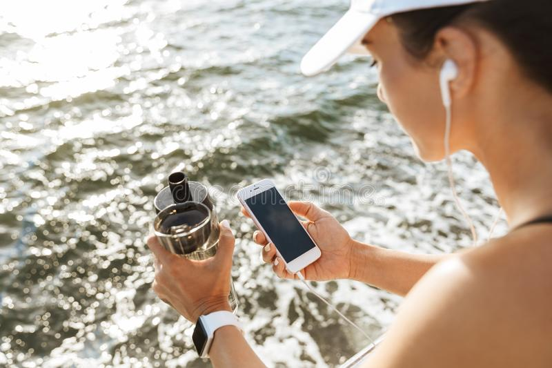 Beautiful young sports fitness woman using mobile phone drinking water at the beach outdoors listening music with earphones. Image of a beautiful young sports royalty free stock photo