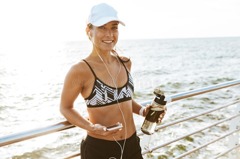 Beautiful young sports fitness woman using mobile phone drinking water at the beach outdoors listening music with earphones. Image of a beautiful young sports stock images