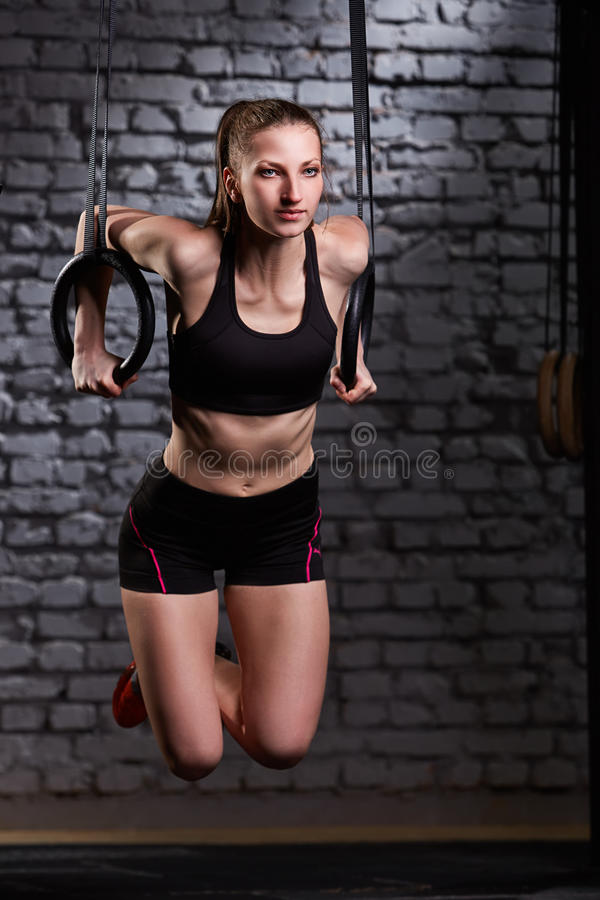 Image of beautiful young sporty woman in the black sportwear doing pull-ups exercise using gymnastic rings. royalty free stock image