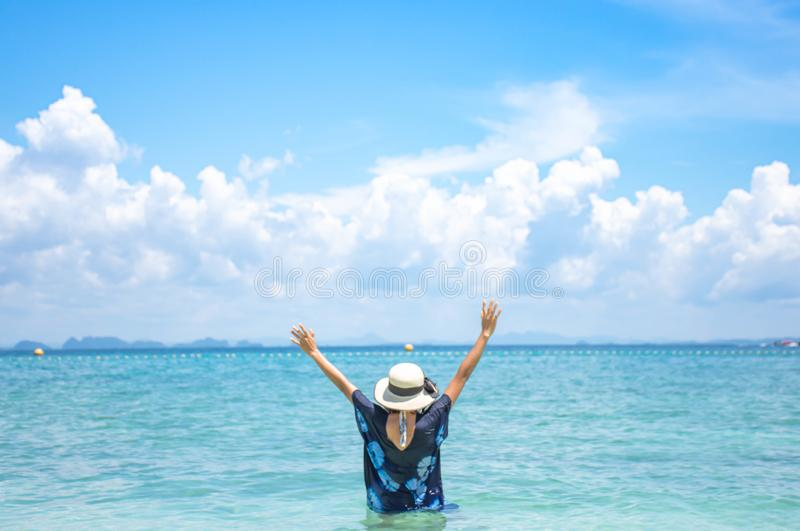 The image behind the woman raise their arms and a hat In the sea background sky and cloud royalty free stock images
