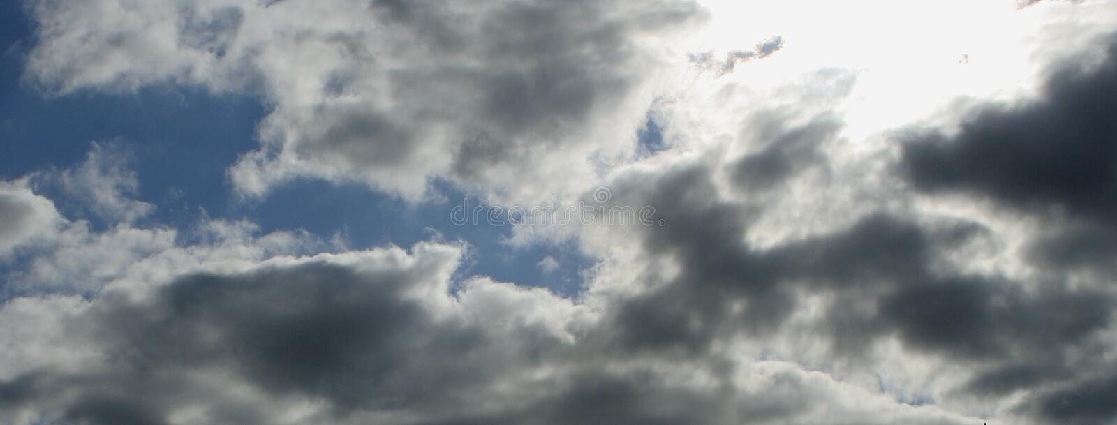 Blue sky with fluffy white and grey clouds, sun shining through stock photography