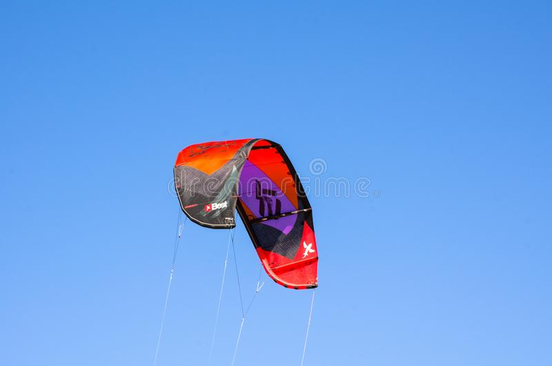 The image of `Best` Kitesurfing sport brand, the kite is in Red, Black and purple flying on the blue sky. royalty free stock photography