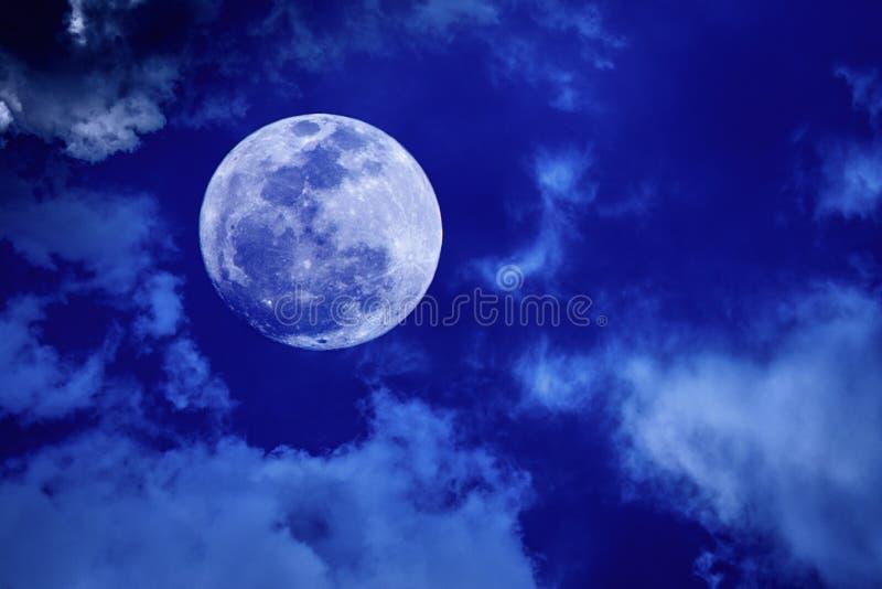 Full Moon in Dark Blue Sky. Image of big bright full moon glowing in the blue sky with dark clouds at night stock image