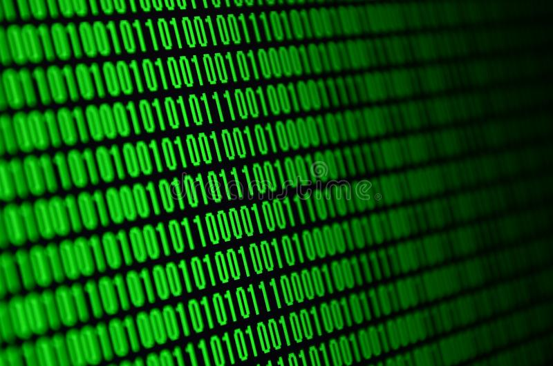 An image of a binary code made up of a set of green digits on a black background.  stock image