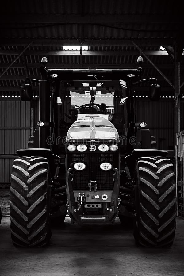 Image black and white of a tractor. A tractor in garage of the farme, black and white, with a top light,  a high horsepower vehicle, in afternoon royalty free stock photography